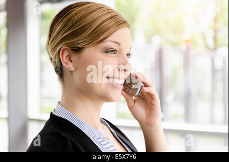 Portrait of young businesswoman chatting on cellphone - Stock Photo