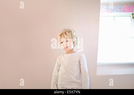 Portrait of four year old boy in bedroom - Stock Photo