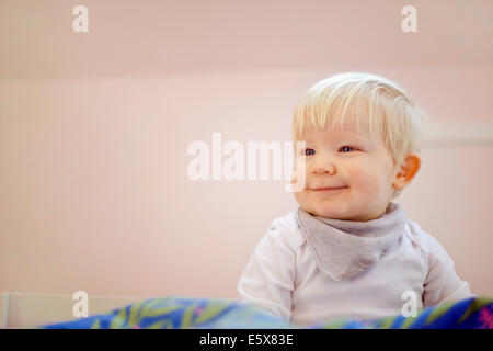 Portrait of cute fourteen month old baby boy sitting on duvet - Stock Photo