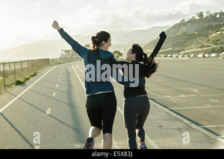 Joggers cheering on road - Stock Photo