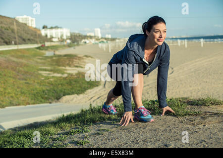 Jogger on her mark by beach - Stock Photo
