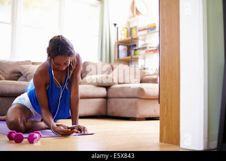Young woman exercising on sitting room floor whilst looking at smartphone - Stock Photo