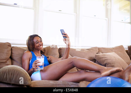 Young woman on a training break, looking at smartphone in sitting room - Stock Photo
