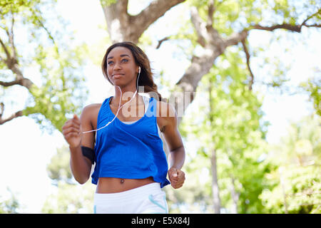 Young female runner running in park - Stock Photo