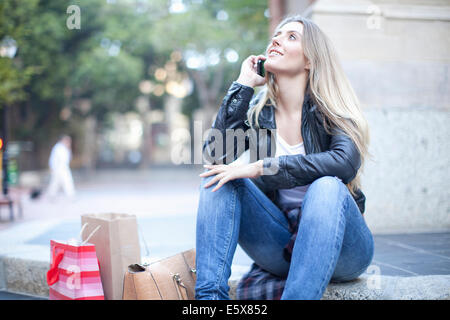 Young woman shopper sitting on city steps chatting on smartphone - Stock Photo