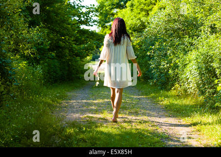 Rear view of young woman strolling barefoot along rural track, Delaware Canal State Park, New Hope, Pennsylvania, - Stock Photo