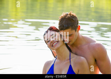Young couple cheek to cheek in river - Stock Photo