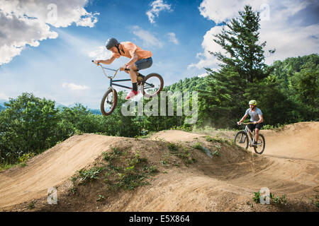 Two male friends riding BMX and mountain bikes on rural pump track - Stock Photo