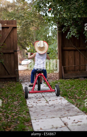 Four year old girl riding her tricycle out of garden gate - Stock Photo