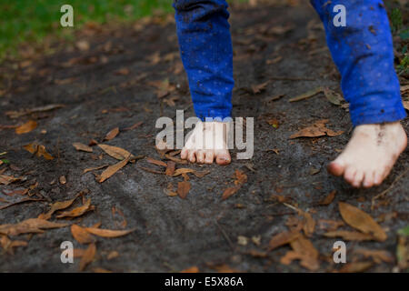 Muddy feet of four year old girl standing in garden soil - Stock Photo