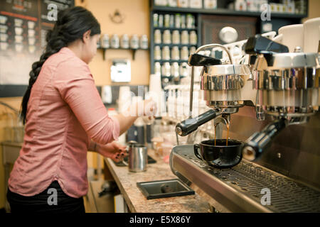 Barista busy with espresso machine in cafe - Stock Photo