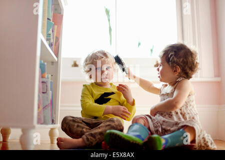 Female toddler brushing male toddlers hair in playroom