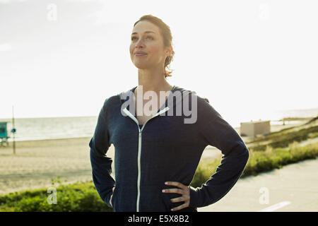 Jogger taking break on road by beach - Stock Photo