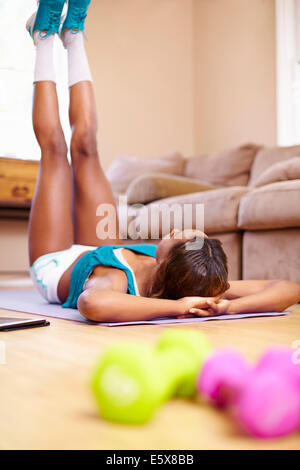 Rear view of young woman exercising on sitting room floor - Stock Photo