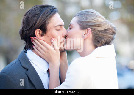 Businessman and woman kissing on city street - Stock Photo