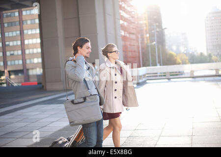 Businessman and woman walking across city rooftop parking lot - Stock Photo