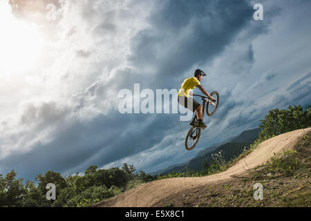 Young male mountain biker jumping mid air on rural pump track - Stock Photo
