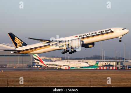 Singapore Airlines Boeing 777-300ER climbs away from runway 05L at Manchester airport. - Stock Photo