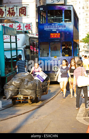 Chinese Female Street Cleaner Pushes A Heavy Cart Of Trash Through Chun Yeung Street, Vintage Hong Kong Tram In - Stock Photo