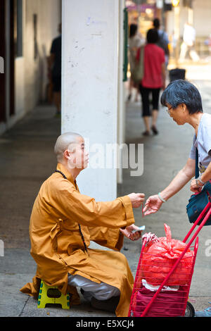 Chinese Woman And A Young Buddhist Monk On Chun Yeung Street, Hong Kong. - Stock Photo