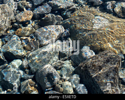 Abstract colourful shallow water ripple patterns above sunlit pebbles in stream bed, Scotland, UK - Stock Photo