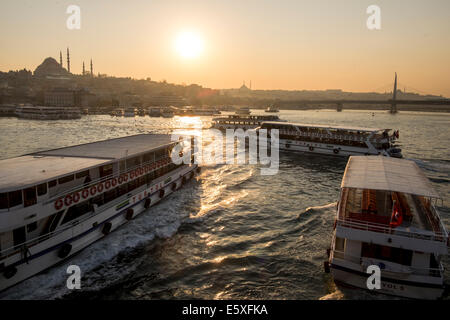 Passenger ships floating on the Golden Horn as the Yavuz Sultan Selim Cami stands out in the horizon in Istanbul, - Stock Photo