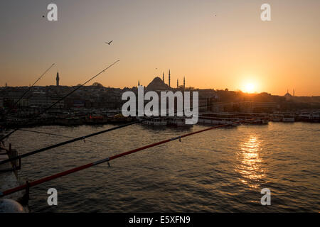 Sunset on the Galata Bridge. In the skyline distinguished the silhouette from Yavuz Selim Mosque. Istanbul, Turkey - Stock Photo