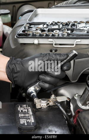 A mechanic tightens a battery terminal cable to a lead battery post. - Stock Photo