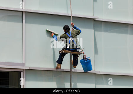 High rise window cleaner  sitting in a bosun's chair - USA - Stock Photo