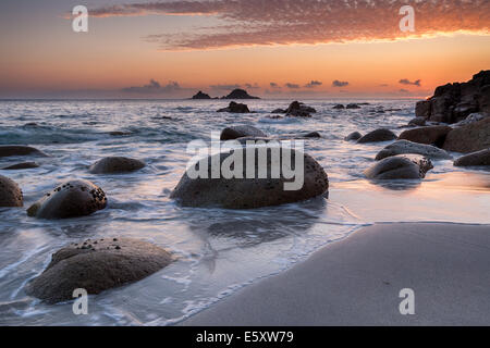 Limpet covered rounded boulders at sunset on a deserted beach at Porth Nanven Cove also known as Cot Valley, near - Stock Photo