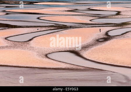 A beach viewed from above showing patterns of sand formed by the sea at low tide. - Stock Photo