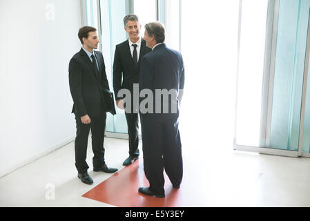 Businessmen chatting in office building lobby - Stock Photo