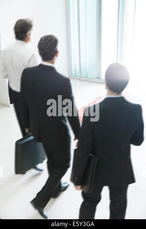 Business associates chatting while leaving office building together - Stock Photo
