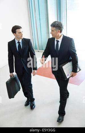 Businessmen passing through office building lobby together - Stock Photo