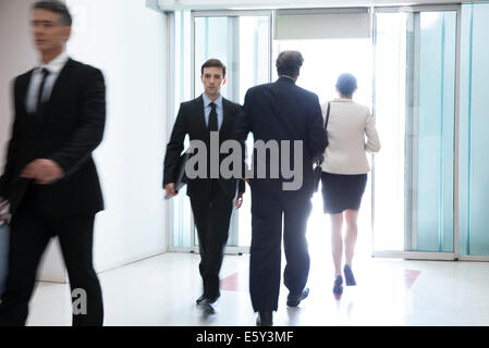 Business professionals passing through office building lobby - Stock Photo