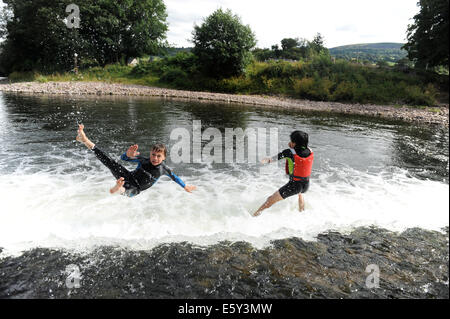 two friends jumping off the weir at Crickhowell bridge in Brecon Beacons in Wales. - Stock Photo
