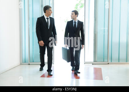 Senior business executive chatting with new associate as they enter building together - Stock Photo