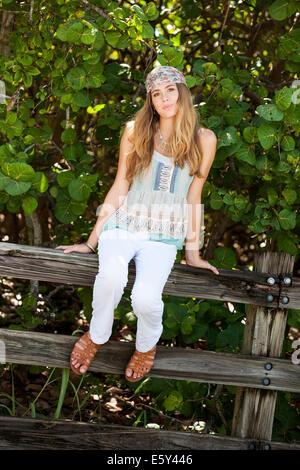 Teenage girl sitting on fence - Stock Photo