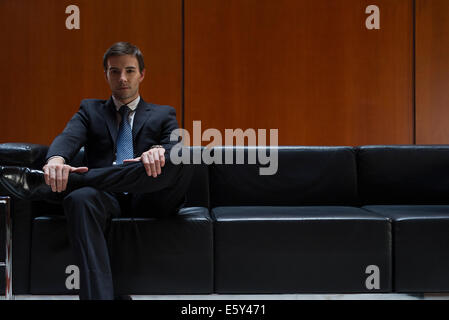 Businessman sitting in waiting room, portrait - Stock Photo