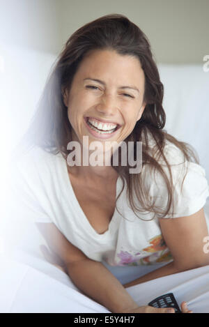 Woman laughing while watching TV in bed - Stock Photo