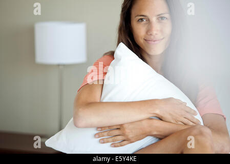 Woman hugging pillow to self, portrait - Stock Photo