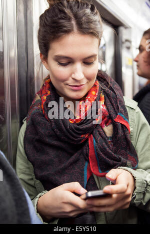 Young woman on subway using smartphone - Stock Photo