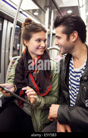 Young couple riding subway together - Stock Photo