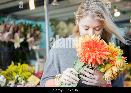 Young woman appreciating flower bouquet fragrance - Stock Photo