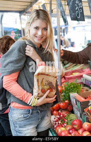 Young woman at greengrocer's buying fresh fruits and vegetables - Stock Photo