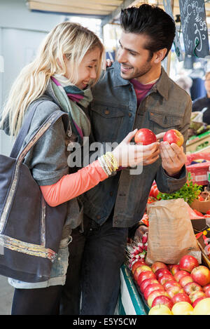Young couple at greengrocer's shopping for fresh fruits and vegetables - Stock Photo