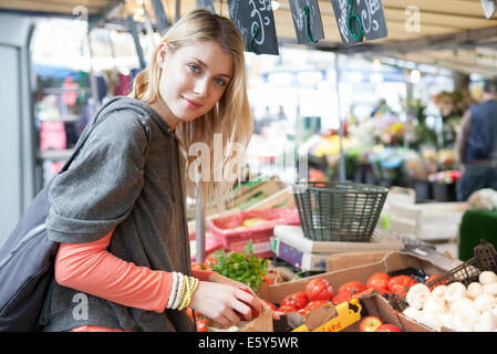 Young woman at greengrocer's shopping for fresh fruits and vegetables - Stock Photo