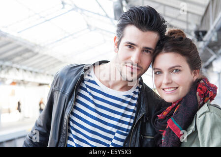 Young couple together on train platform, portrait - Stock Photo