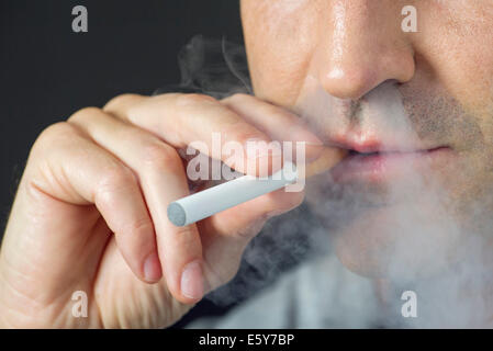Man smoking electonic cigarette, cropped - Stock Photo