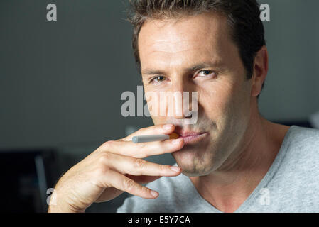 Man smoking electonic cigarette, portrait - Stock Photo